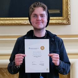 Riley Brown receives his National Vocational Qualification certificate.