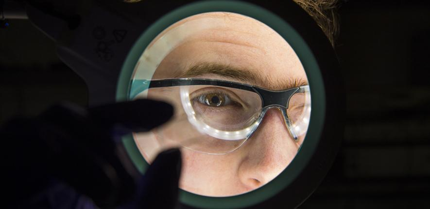 A scientist viewing a microfluidic chip.